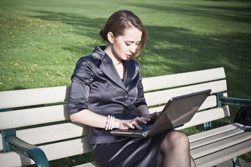 Businesswoman sitting on bench working on laptop in park