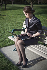 Business woman sitting on bench working on laptop in park