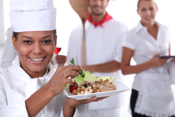a cook holding a dish, a pizza cook and a waitress
