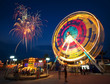Amusement park at night - ferris wheel  in motion and firework