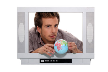 man behind a television screen is taking a little globe
