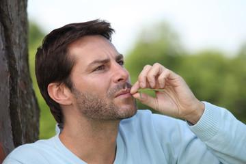 Man chewing ongrass