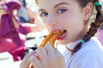 Blue eyes little girl eating churros smiling