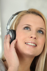 Blond girl listening to music through headphones
