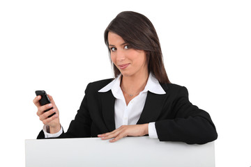 Businesswoman with mobile posing by blank poster