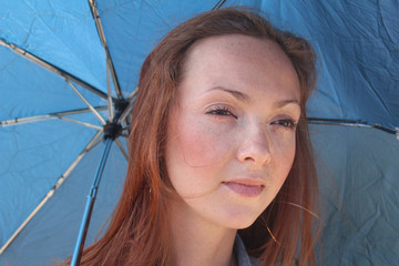 Redhead young woman with an umbrella