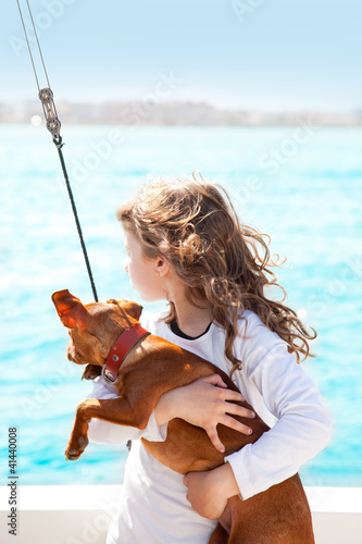 brunette kid girl with dog on the sea