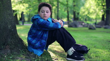 Young sad, depressed boy sitting by the tree in park