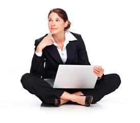 Young business woman sitting on the floor with laptop, thinking