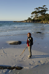 Woman at Binalong Bay drawing heart in sand, Tasmania