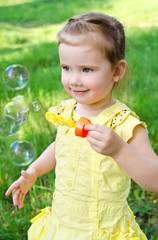 Portrait of little girl blowing soap bubbles