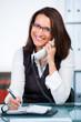 geschäftsfrau mit brille vergibt einen termin am telefon