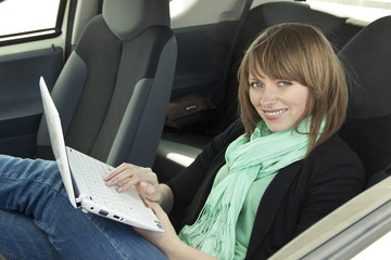 Young woman enjoy by using laptop in the car
