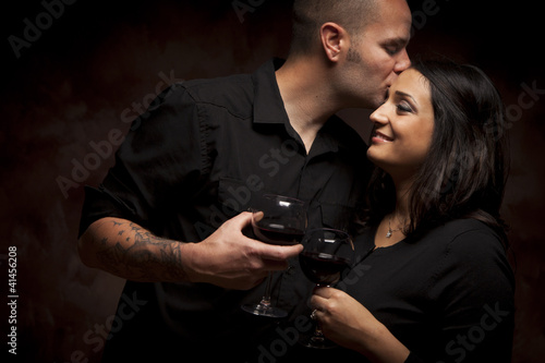 Happy Mixed Race Couple Flirting and Holding Wine Glasses