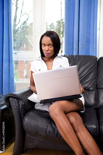 Beautiful young woman with laptop online at home