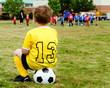 Boy  watching organized youth soccer game from sidelines