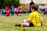 Boy watching organized youth soccer game