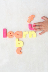 Fun learning the ABC, with child hand forming a word puzzle