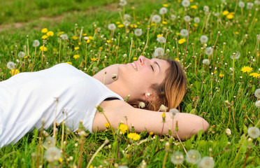 Spring: young, pretty woman relaxing in meadow with dandelions 2