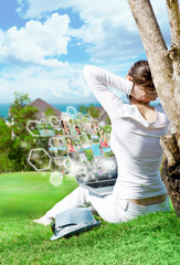 Young woman sitting under tree with laptop and dreaming. Idyllic