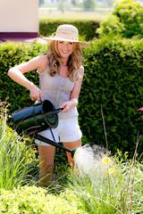 Frau gießt Blumen im Garten mit Gießkanne