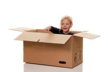 Kind in Umzugskarton. Liegt beim Umzug in Schachte
