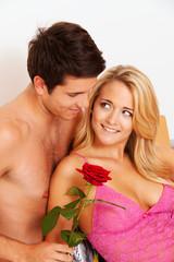 Romatisches Paar im Bett mit Rose.