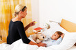 Mutter und krankes Kind im Bett.