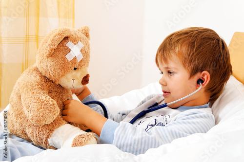 Krankes Kind untersucht Teddy mit Stethoskop