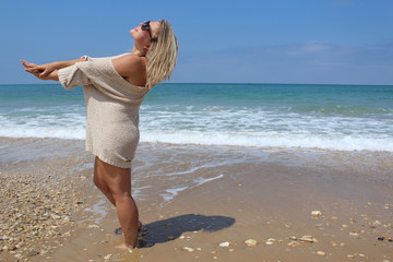 Blonde woman at the beach, stretching hands