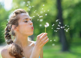 Young woman blowing away dandelion