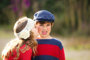 little girl giving kiss to young embarrassed boy.
