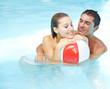 Paar mit Wasserball entspannt im Pool
