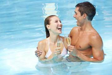 Lachendes Paar mit Sekt im Pool