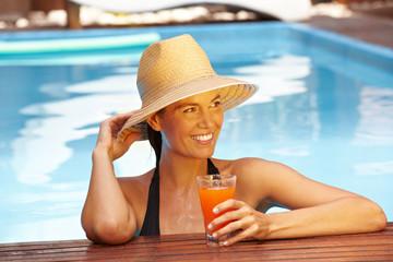 Frau mit Strohhut am Pool