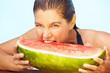 Frau beißt in Melonenstück