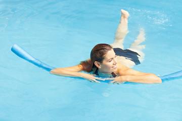 Frau schwimmt mit Schwimmnudel
