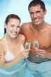 Paar im Pool stößt mit Sekt an