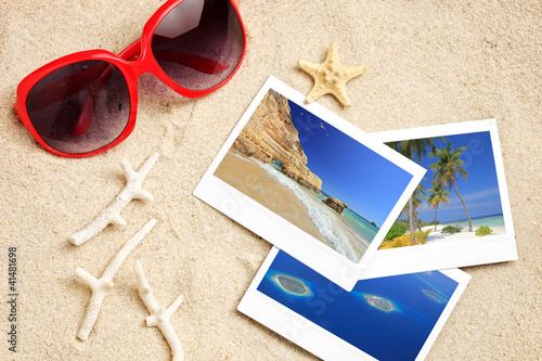 A sunglasses, few photos, starfish and corals on a beach