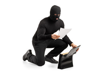 A thief reading a confidential documents after stealing a briefc