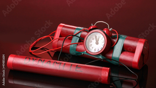 Timebomb made of dynamite on red background