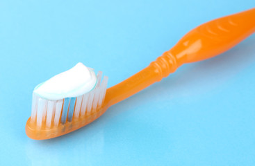 Toothbrush with paste on blue background