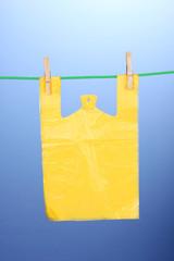 Cellophane bag hanging on rope on blue background