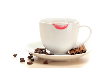 cup of coffee with lipstick mark beans and cinnamon sticks