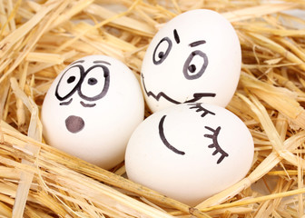 White eggs with funny faces in straw
