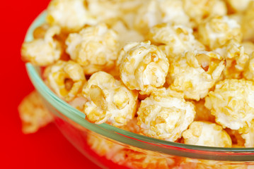 Popcorn in the bowl on red background