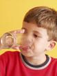Niño bebiendo un vaso de agua en una cocina.