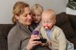 Mutter mit zwei Kindern zeigt etwas auf dem Smartfon