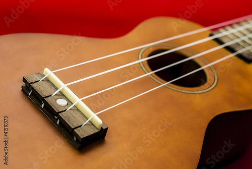 Vintage ukulele on red background
