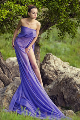 young woman in purple long dress standing on stone near tree
